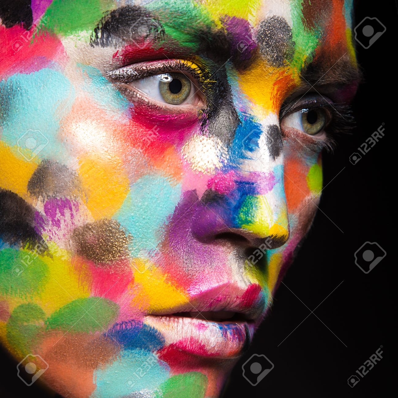 Girl with colored face painted. Art beauty image. Picture taken in the studio on a black background. - 43728649