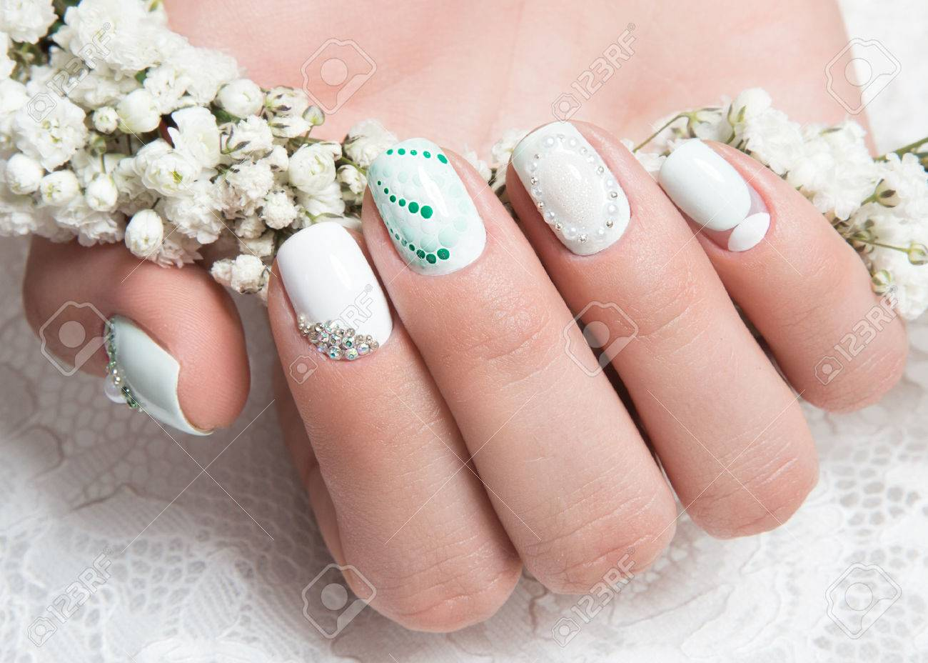 Wedding manicure for the bride in gentle tones with flowers wedding manicure for the bride in gentle tones with flowers nail design stock photo prinsesfo Images