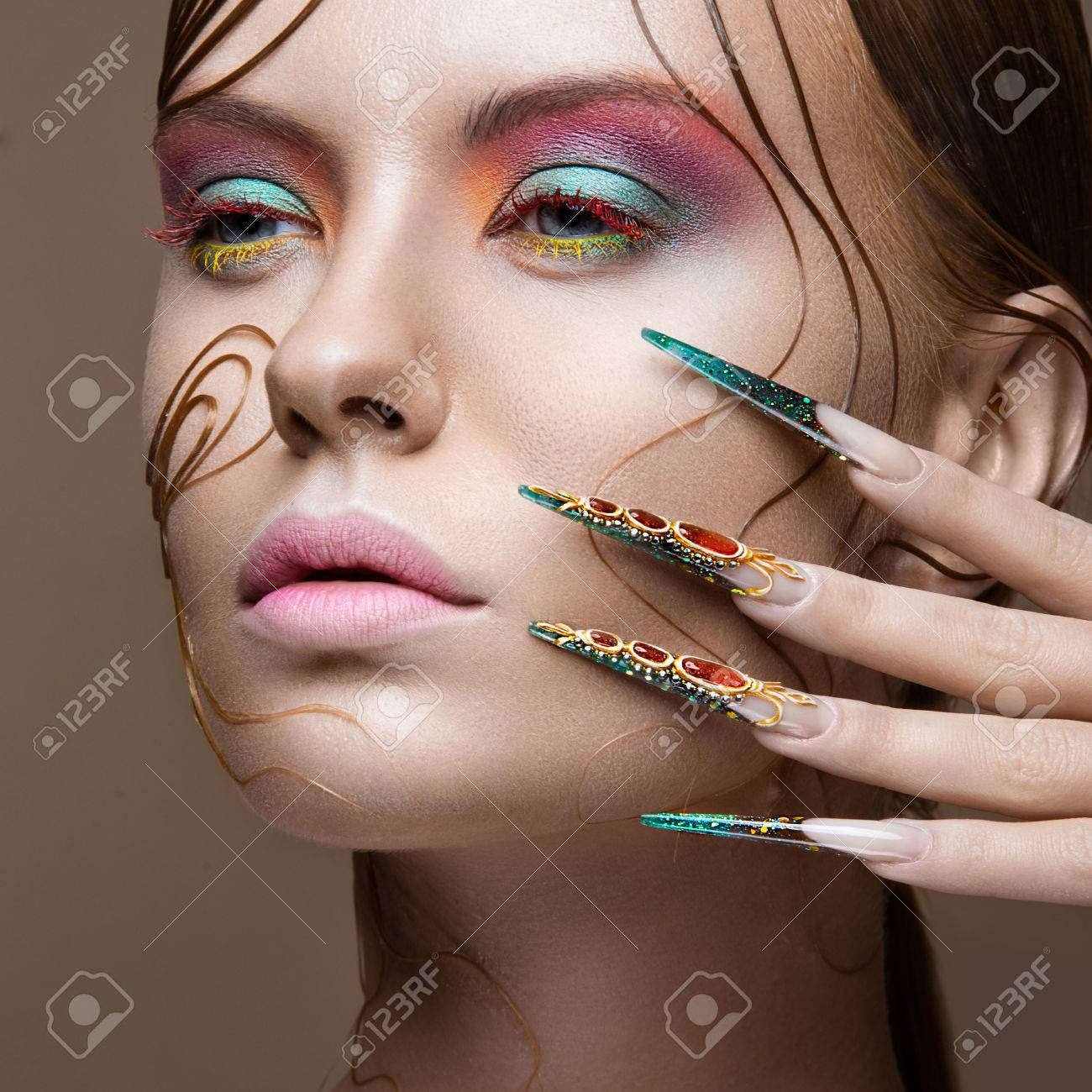 Beautiful girl with bright fashion make-up, creative hairstyle, long nails. Design manicure. Beauty face. Picture taken in the studio. - 45415627