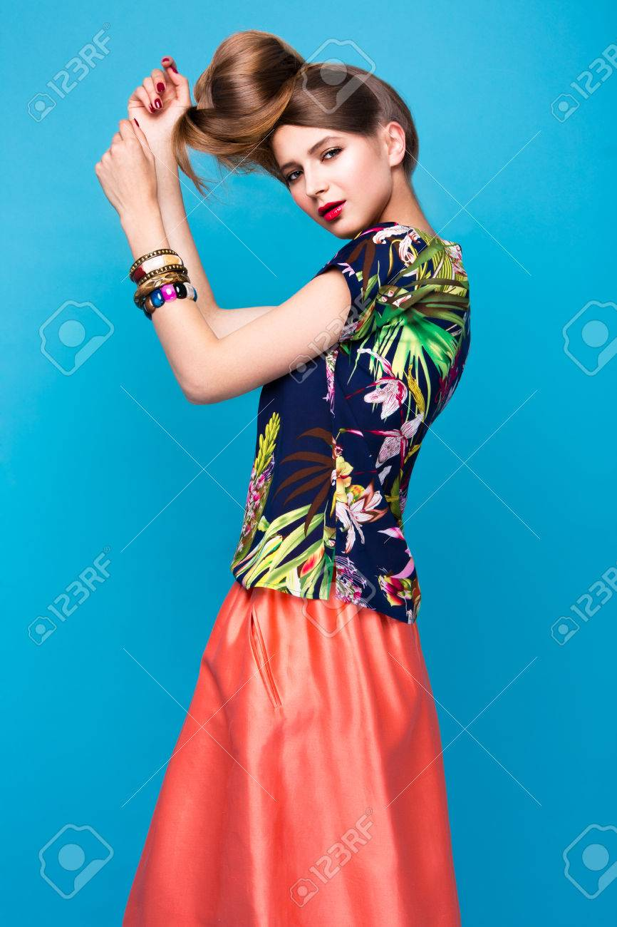 Beautiful fashionable woman an unusual hairstyle in bright clothes and colorful accessories. Cuban style. Picture taken in the studio on a bright background. - 45870849