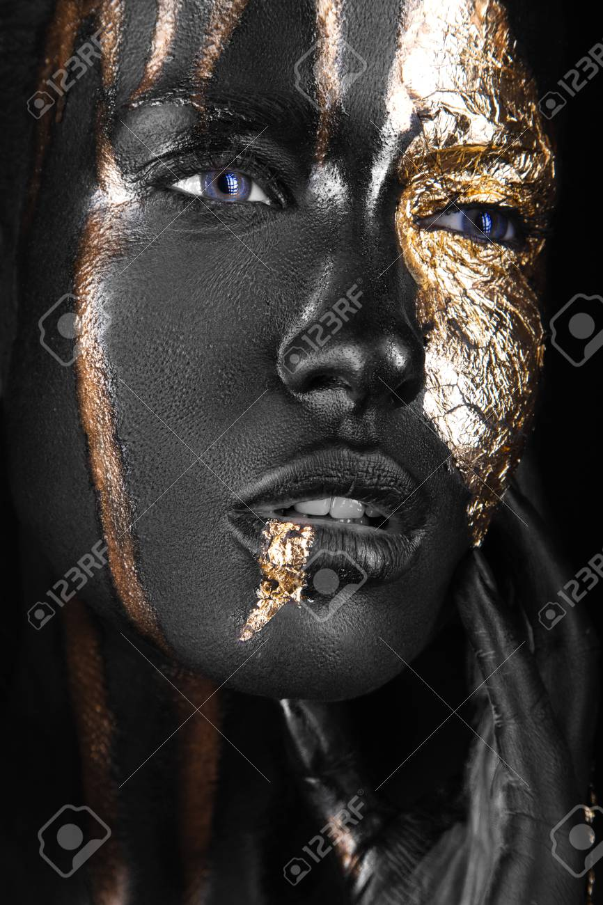 fashion portrait of a dark-skinned girl with gold make-up.Beauty face. Picture taken in the studio on a black background. - 46044112