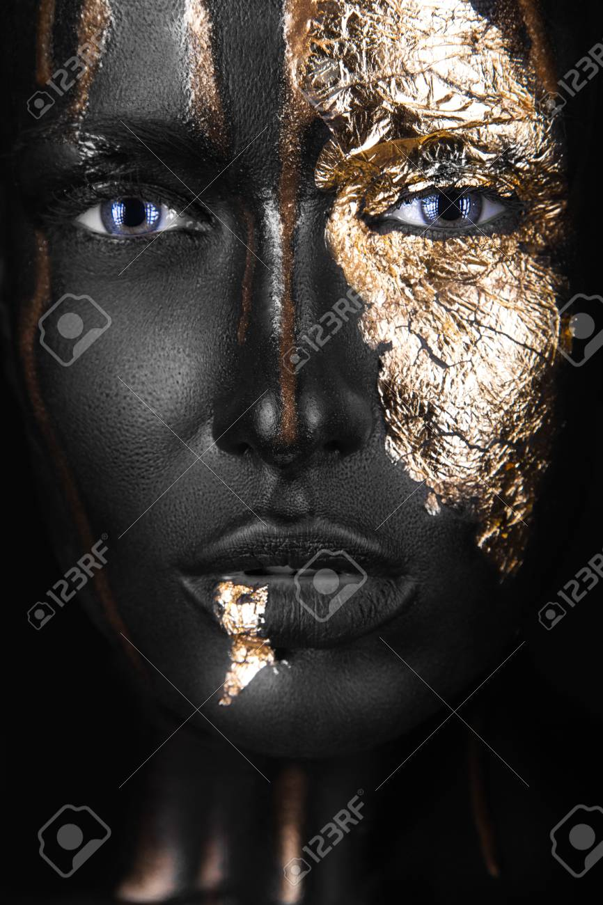 fashion portrait of a dark-skinned girl with gold make-up.Beauty face. Picture taken in the studio on a black background. - 46044118