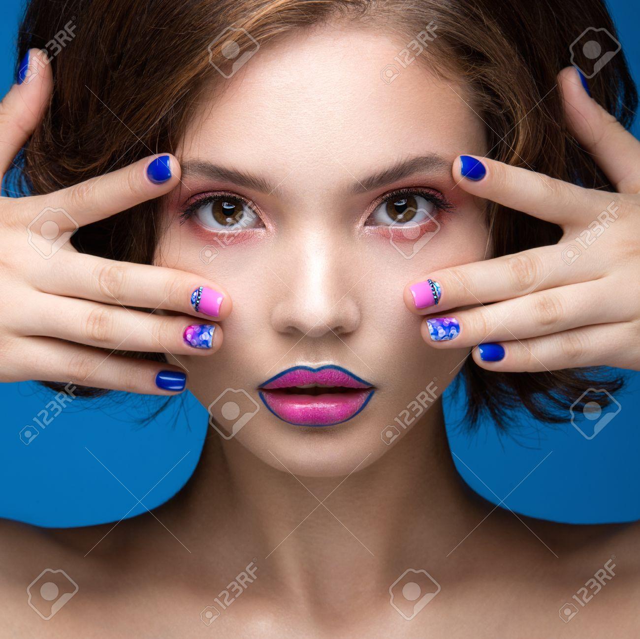 写真素材 , 明るいメイクやネイルの色と美しいモデルの女の子。美容顔。短いカラフルな爪。青色の背景のスタジオでの撮影。