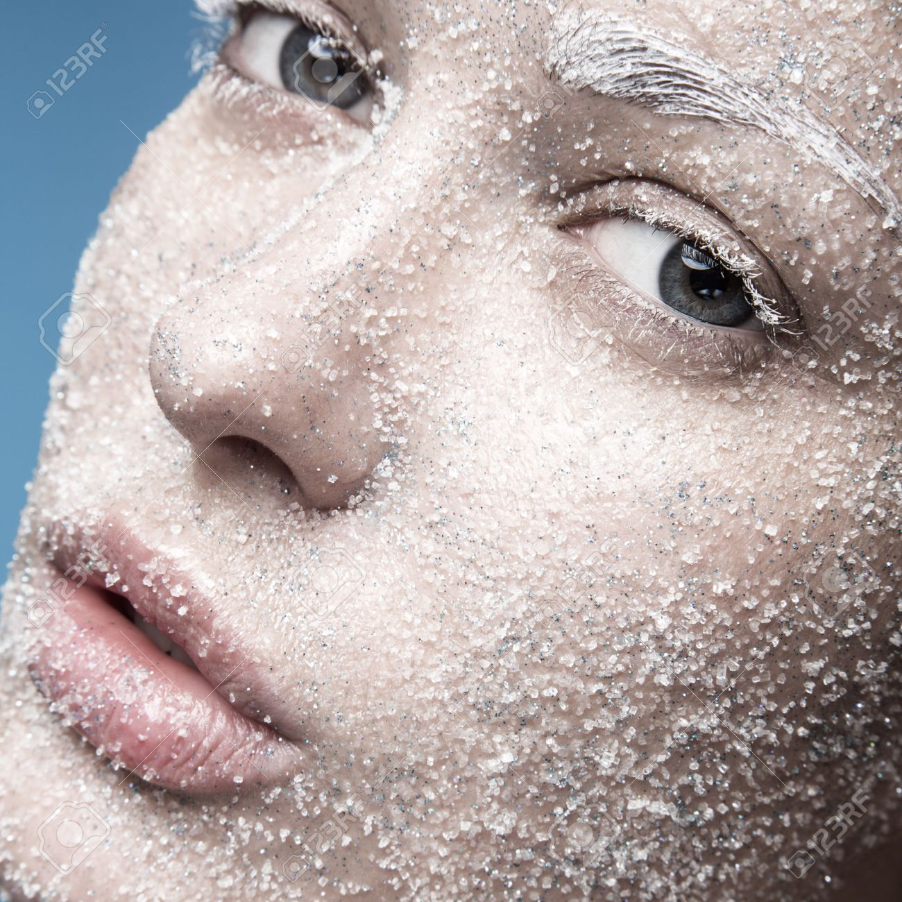 Portrait of a girl with pale skin and sugar snow on her face. Creative art beauty fashion. Picture taken in the studio on a blue background. - 46801124