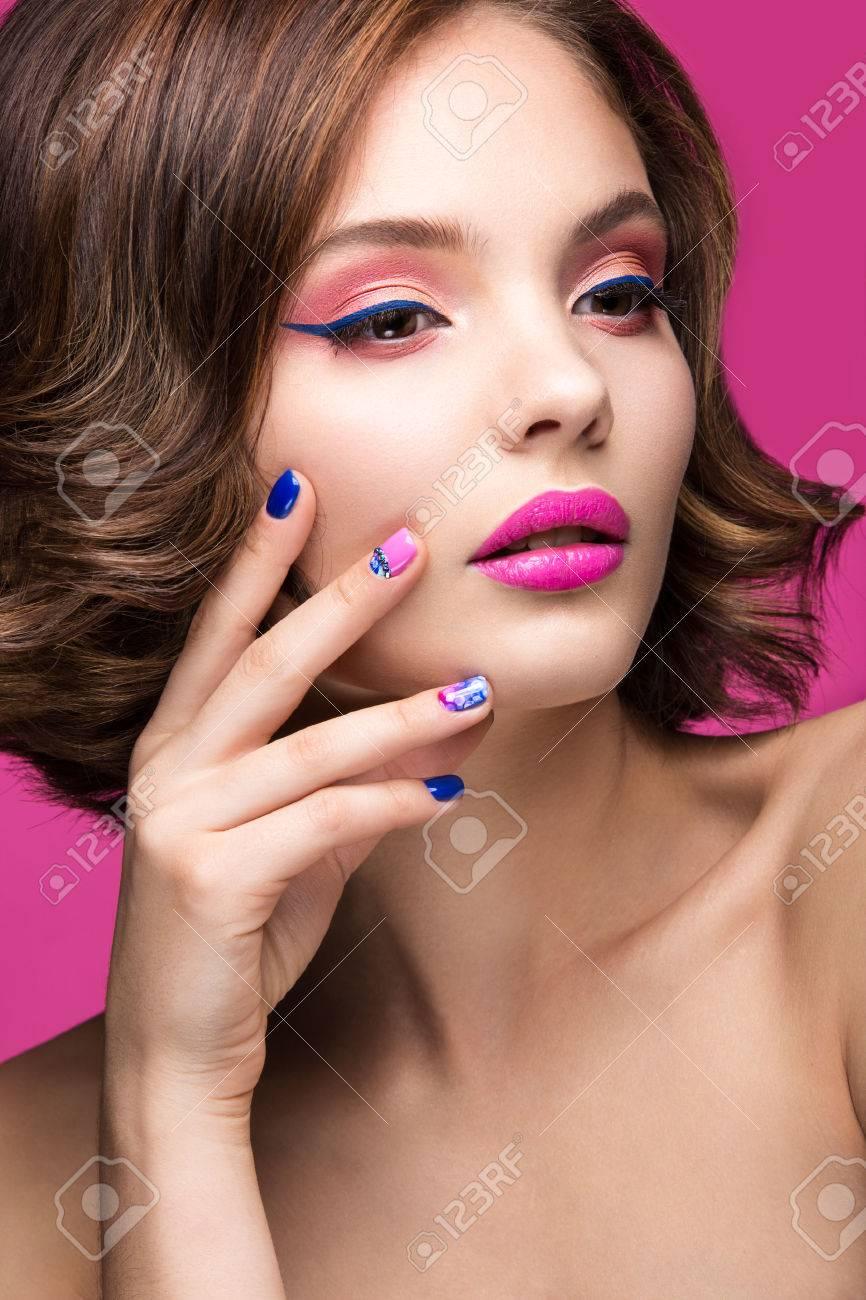 写真素材 , 明るいメイクやネイルの色と美しいモデルの女の子。美容顔。短いカラフルな爪。ピンクの背景のスタジオでの撮影。