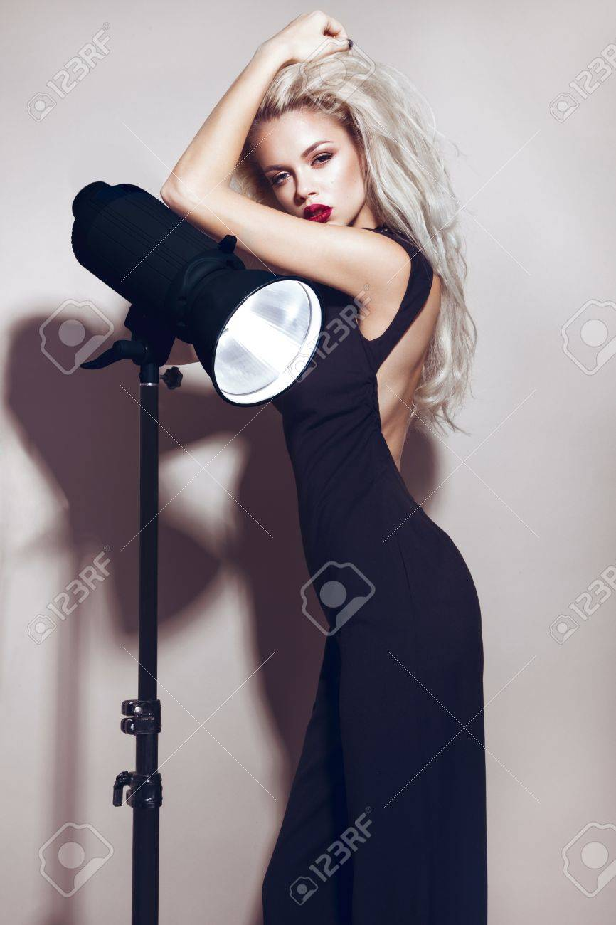 Beautiful blonde girl with sensual lips, fashion hair, black dress and gold accessories. Beauty face. Picture taken in the studio - 48761186