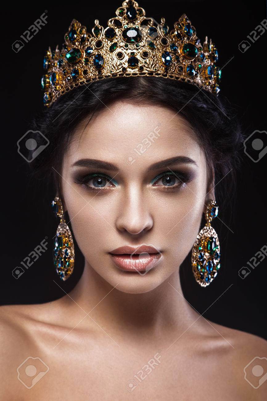 Beautiful brunette girl with a golden crown and earrings and professional evening make-up. Beauty face. Picture taken in the studio. - 49409806