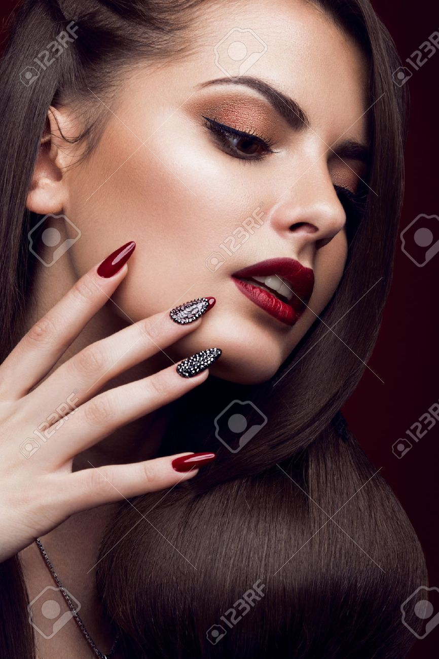 Pretty girl with unusual hairstyle, bright makeup, red lips and manicure design. Beauty face. Art nails. Picture taken in the studio on a red background. - 50899024