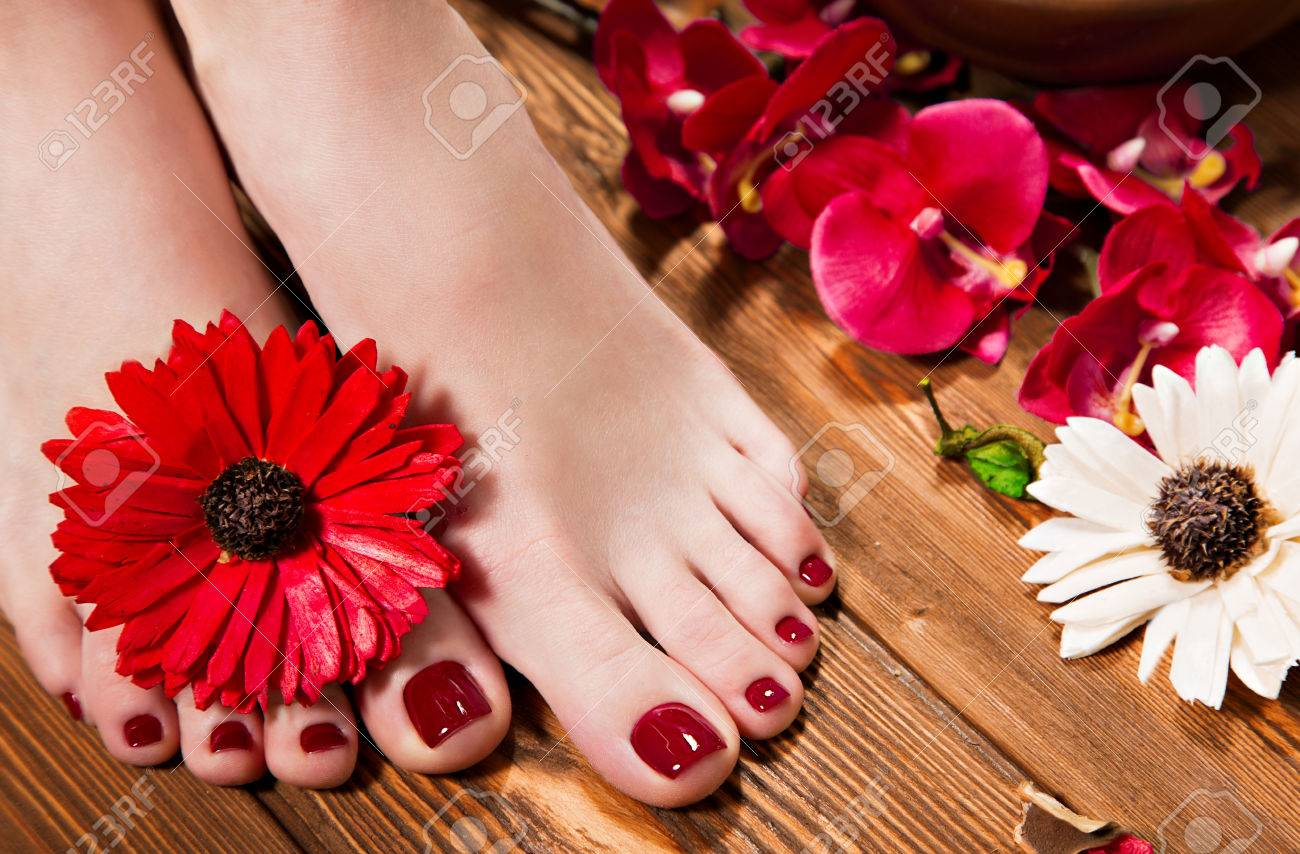 Beautiful classic red pedicure on female hand. Close-up. Picture taken in the studio on the background of flowers - 57242933