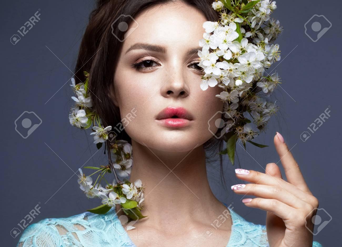 Hermosa Chica Morena En Vestido Azul Con Un Suave Maquillaje Romántico Labios Rosados Y Flores La Belleza De La Cara Retrato De Un Disparo En El