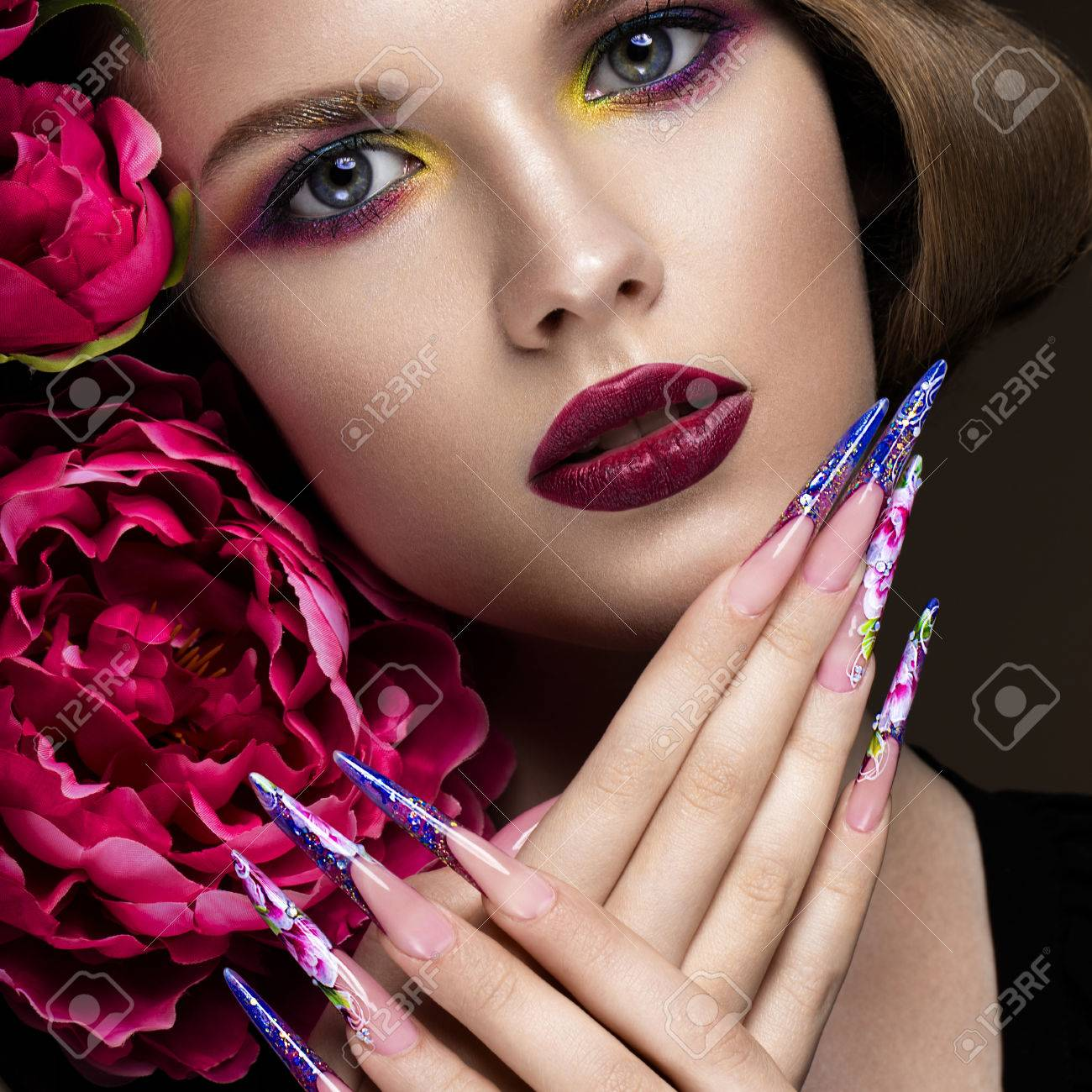 Beautiful girl with colorful make-up, flowers, retro hairstyle and long nails. Manicure design. The beauty of the face. Photos shot in studio - 57853909