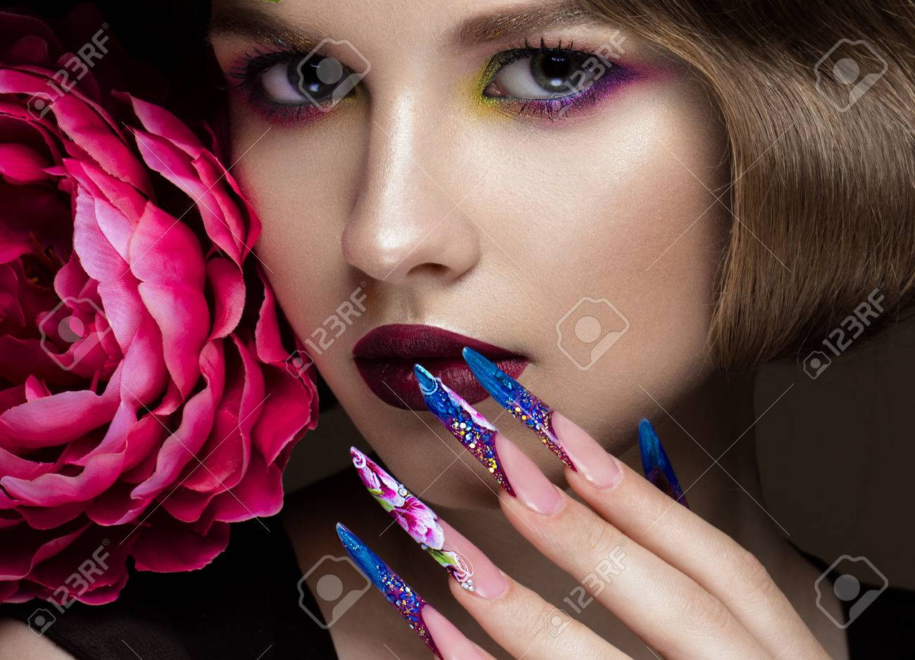 Beautiful girl with colorful make-up, flowers, retro hairstyle and long nails. Manicure design. The beauty of the face. Photos shot in studio - 57853907