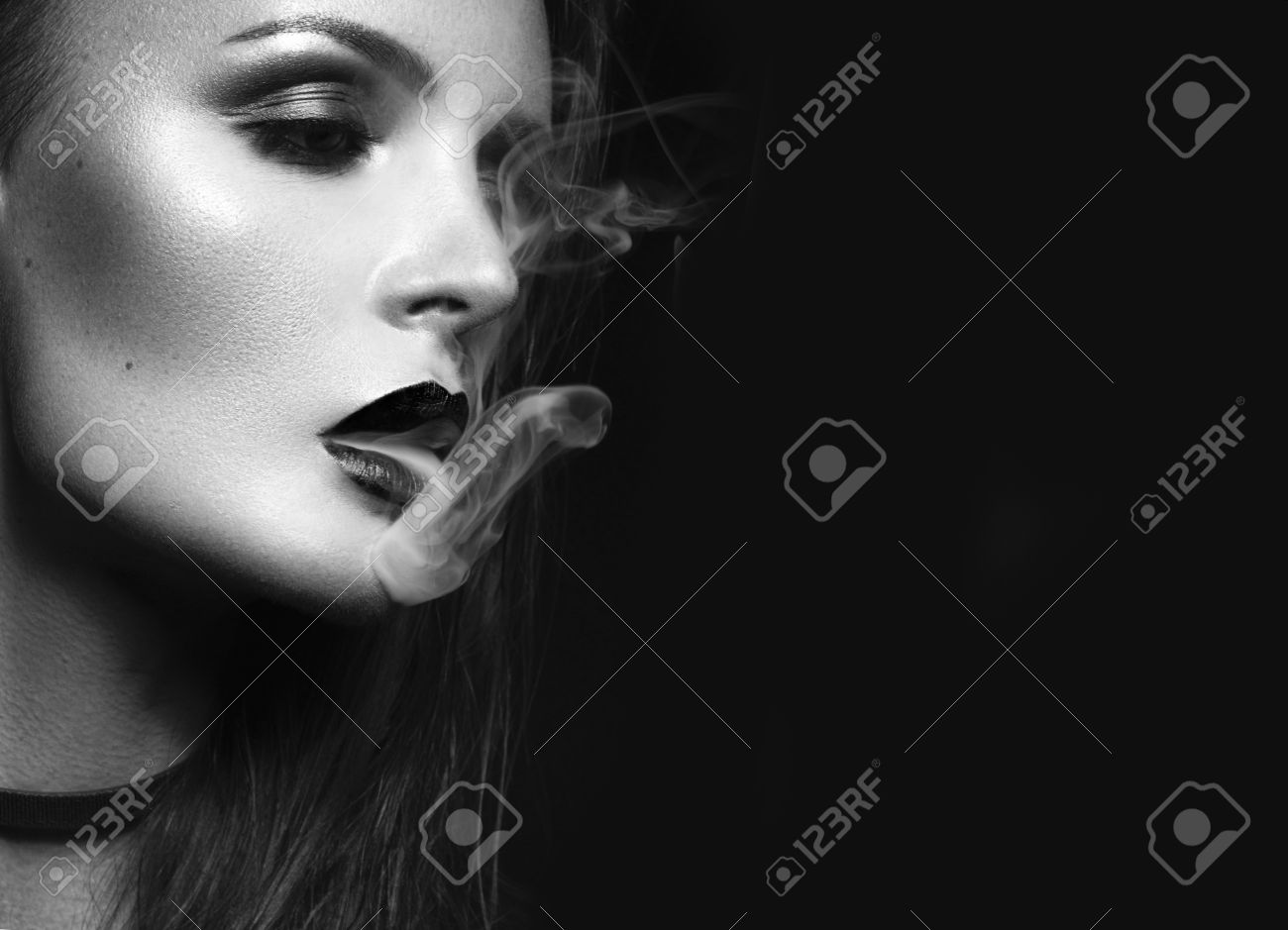 Beautiful brunette girl with bright makeup, red lips, smoking with smoke from mouth. beauty face. Black and white. Photos shot in the studio on a black background. - 60569985