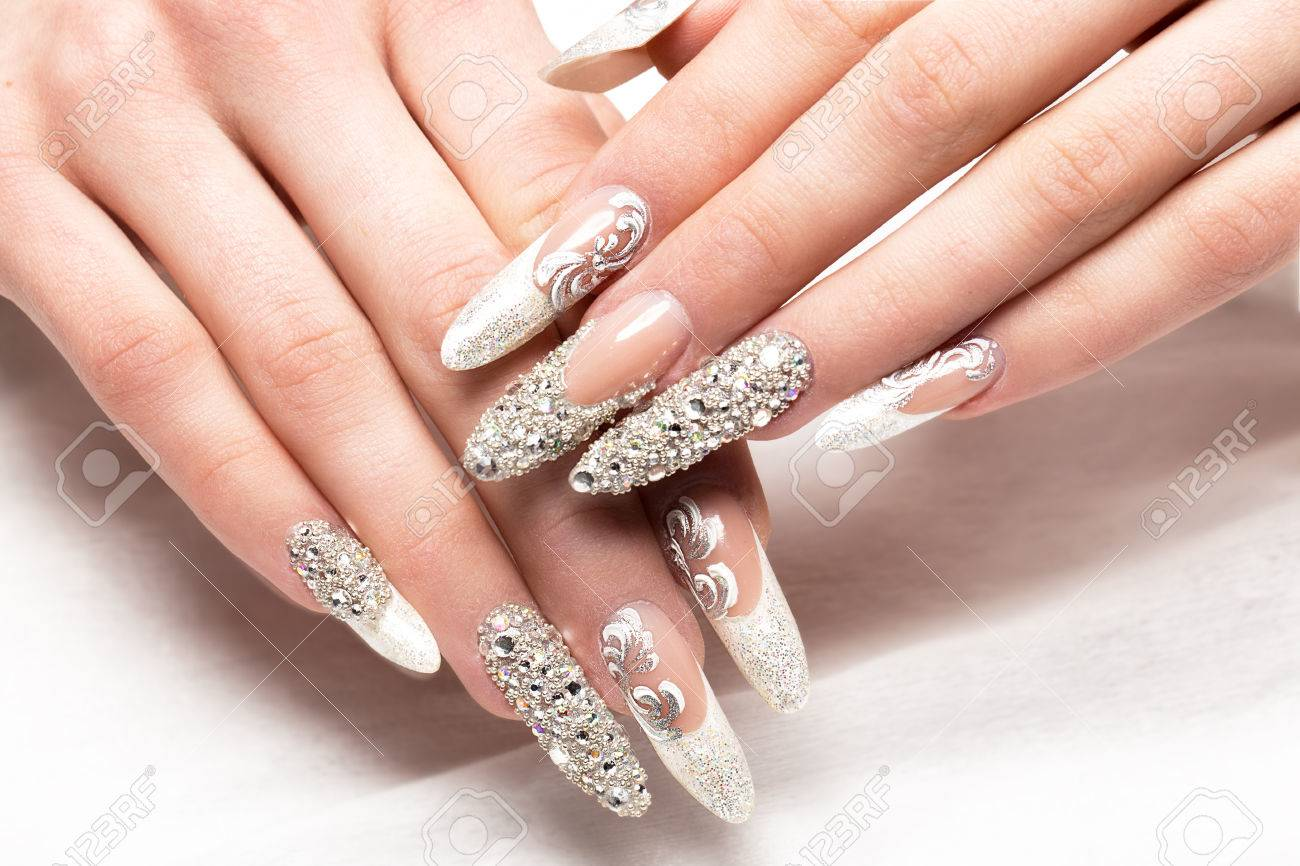 Beautifil wedding manicure for the bride in gentle tones with rhinestone. Nail Design. Close-up. - 65372823