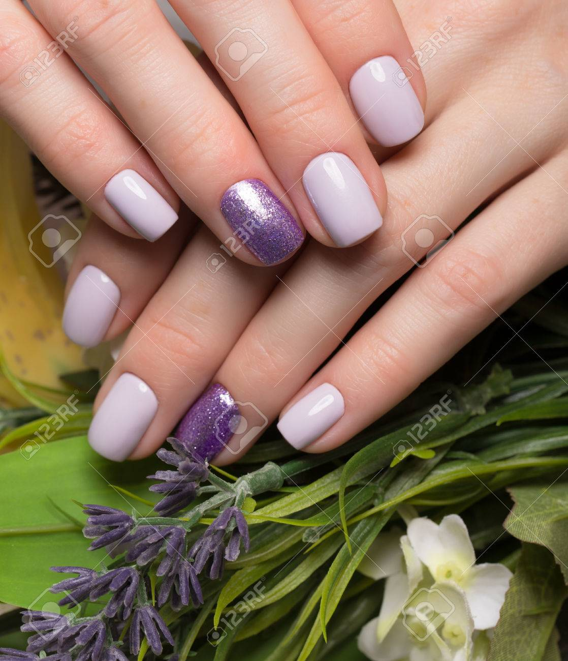Manicura Aseada Purpura En Las Manos Femeninas En Un Fondo De Flores