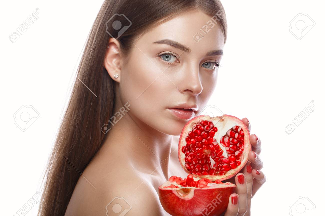 Beautiful young girl with a light natural make-up and perfect skin with pomegranate in her hand. Beauty face. Picture taken in the studio on a white background. - 95363309