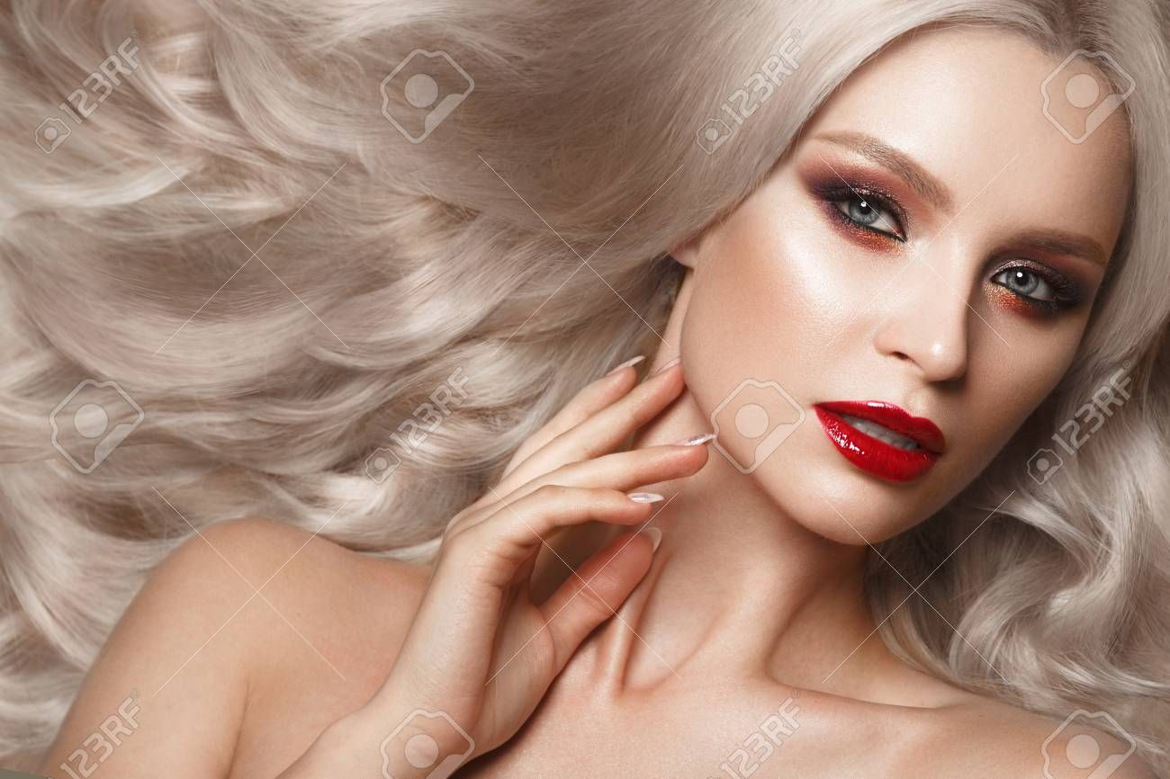 Beautiful blonde in a Hollywood manner with curls, natural makeup and red lips.
