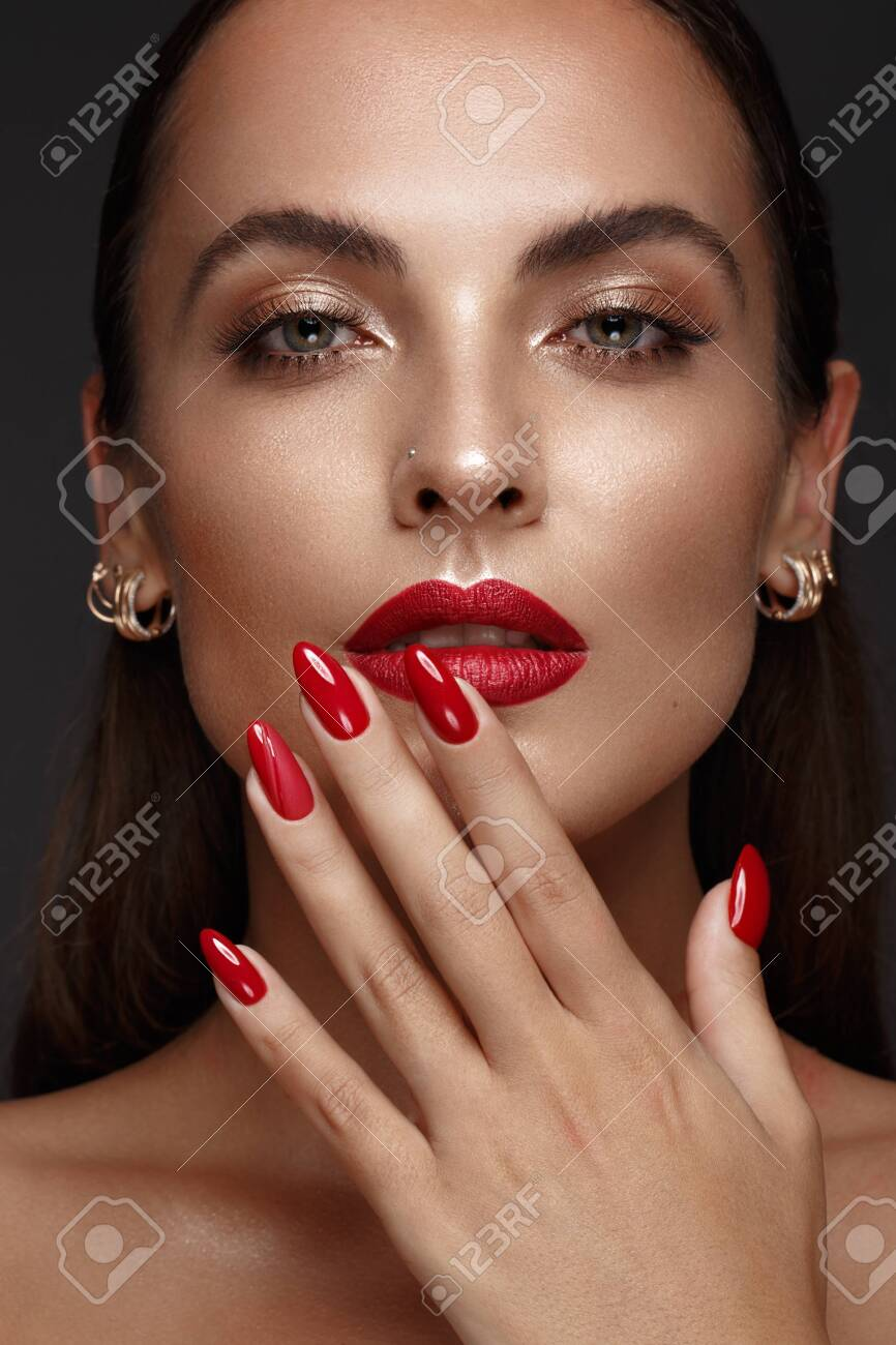 Beautiful girl with a classic make up and multi-colored nails. Manicure design. Beauty face. Photo taken in the studio - 137116593