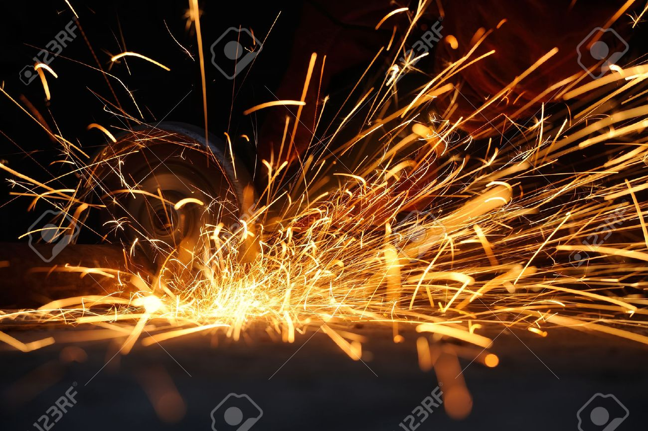 Worker cutting metal with grinder. Sparks while grinding iron Standard-Bild - 38877772