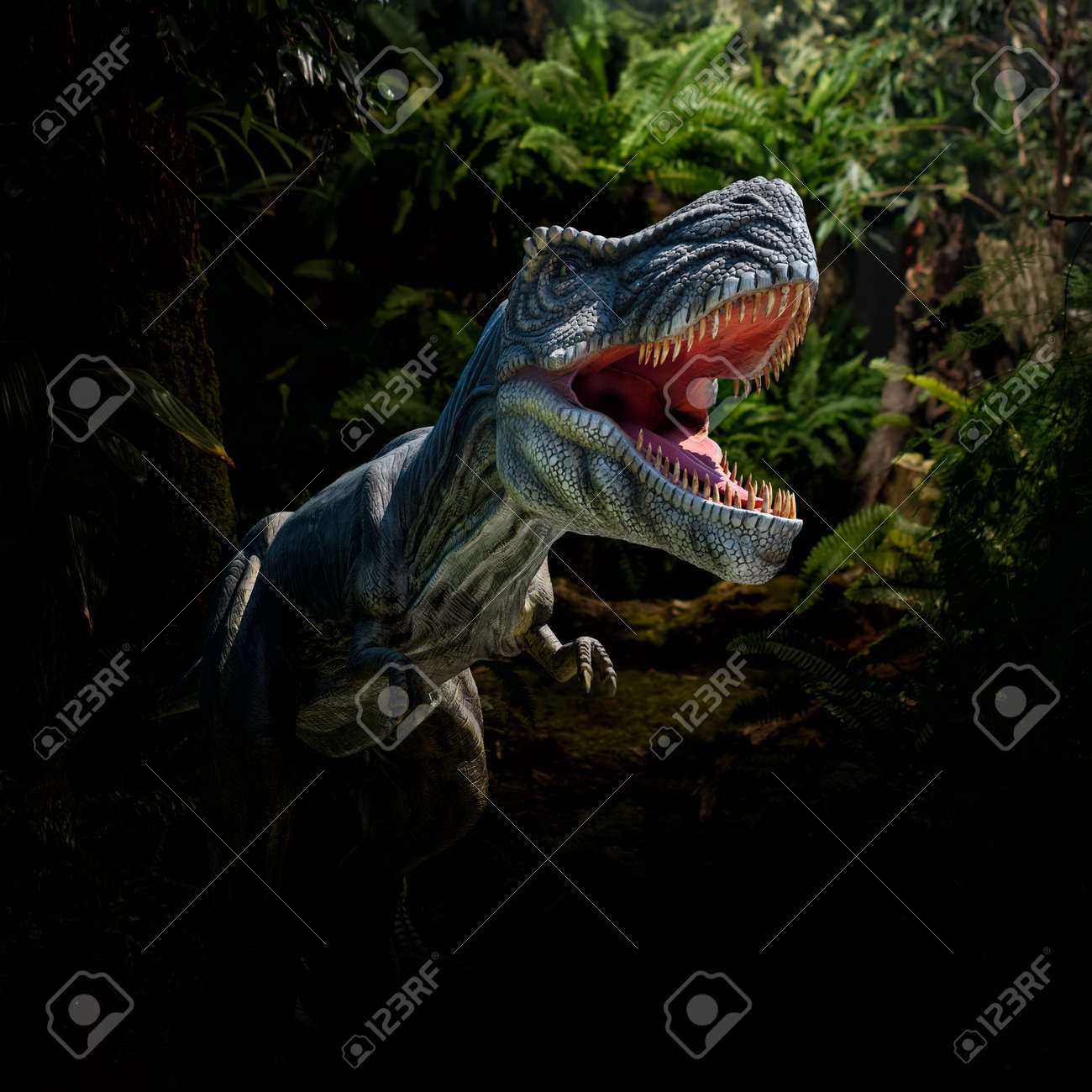 Closeup view of an angry T-Rex dinosaur figurine in jungle. Monstrous animal with open mouth and sharp teeth - 161598284