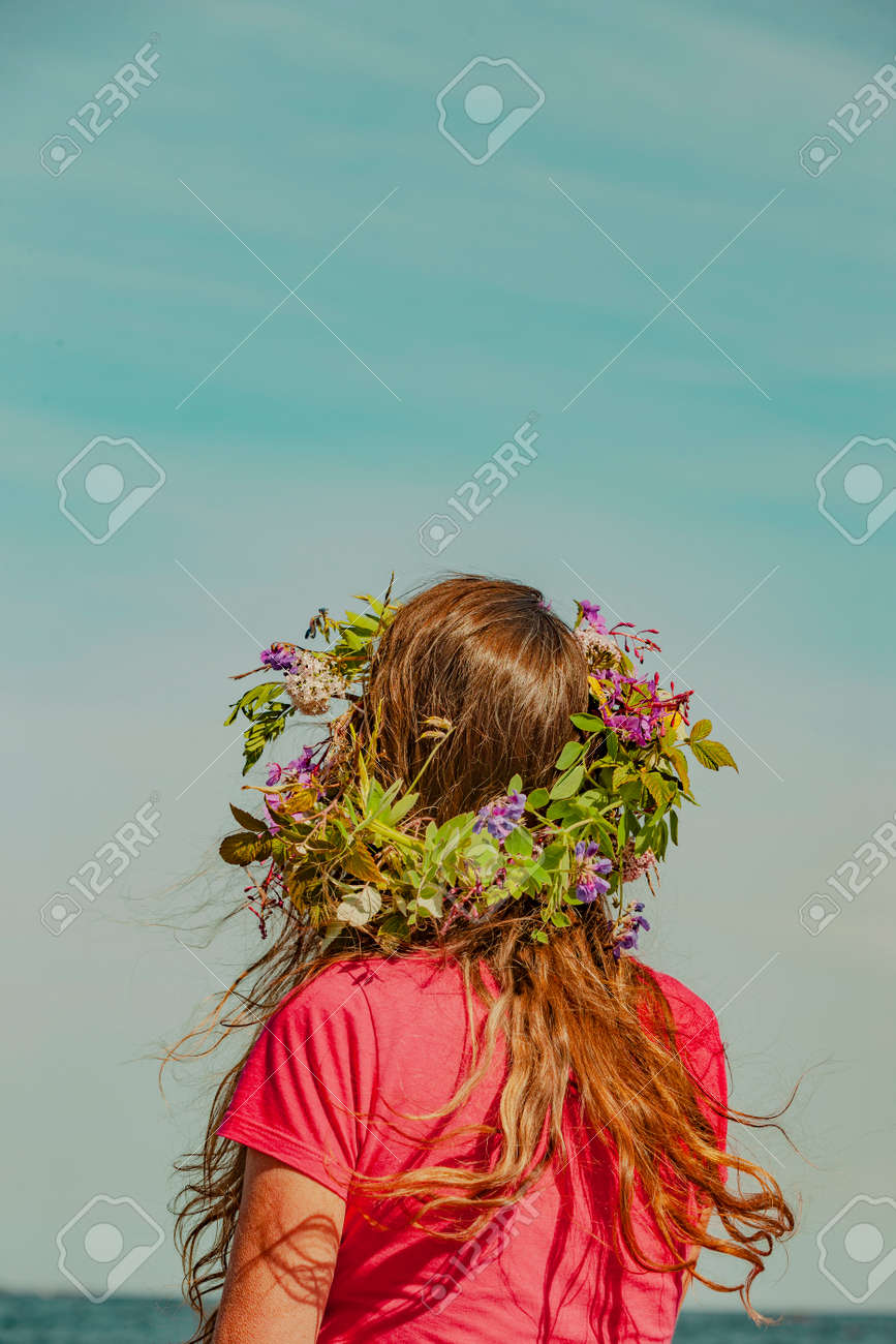 Brunette woman with wreath of flowers in Sweden - 169244995