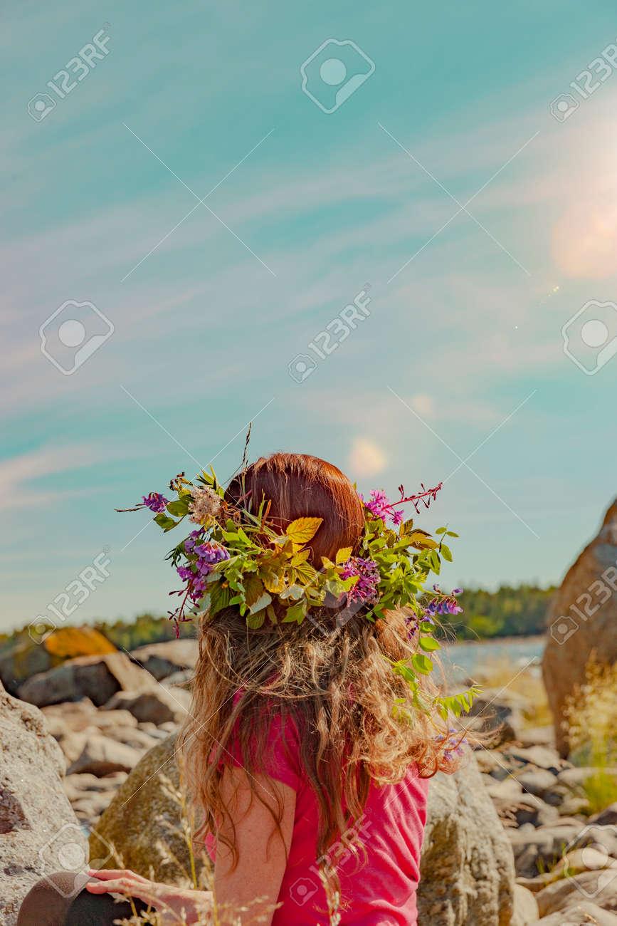 Brunette woman with wreath of flowers in Sweden - 169245000