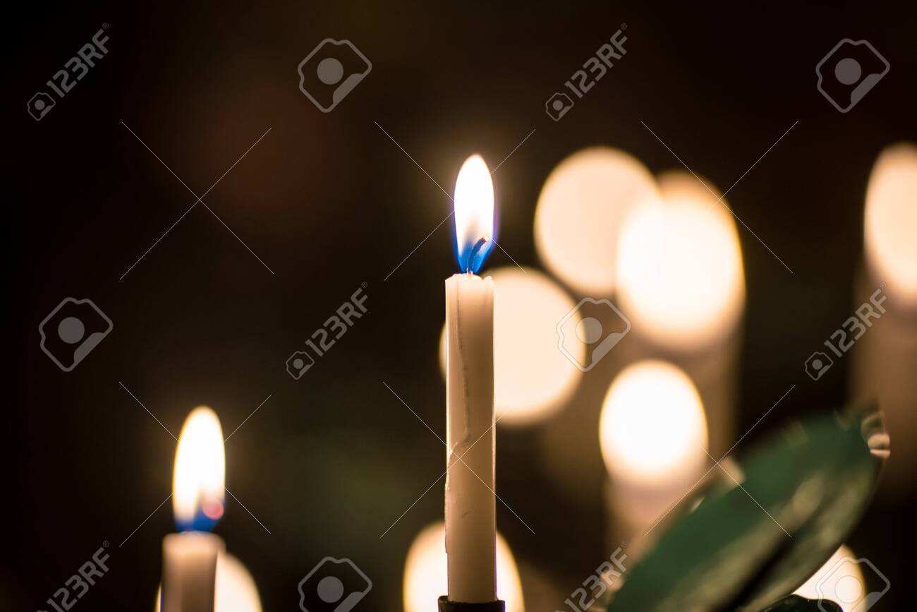 Many burning church wax yellow candles in large on a special stand - 126575175
