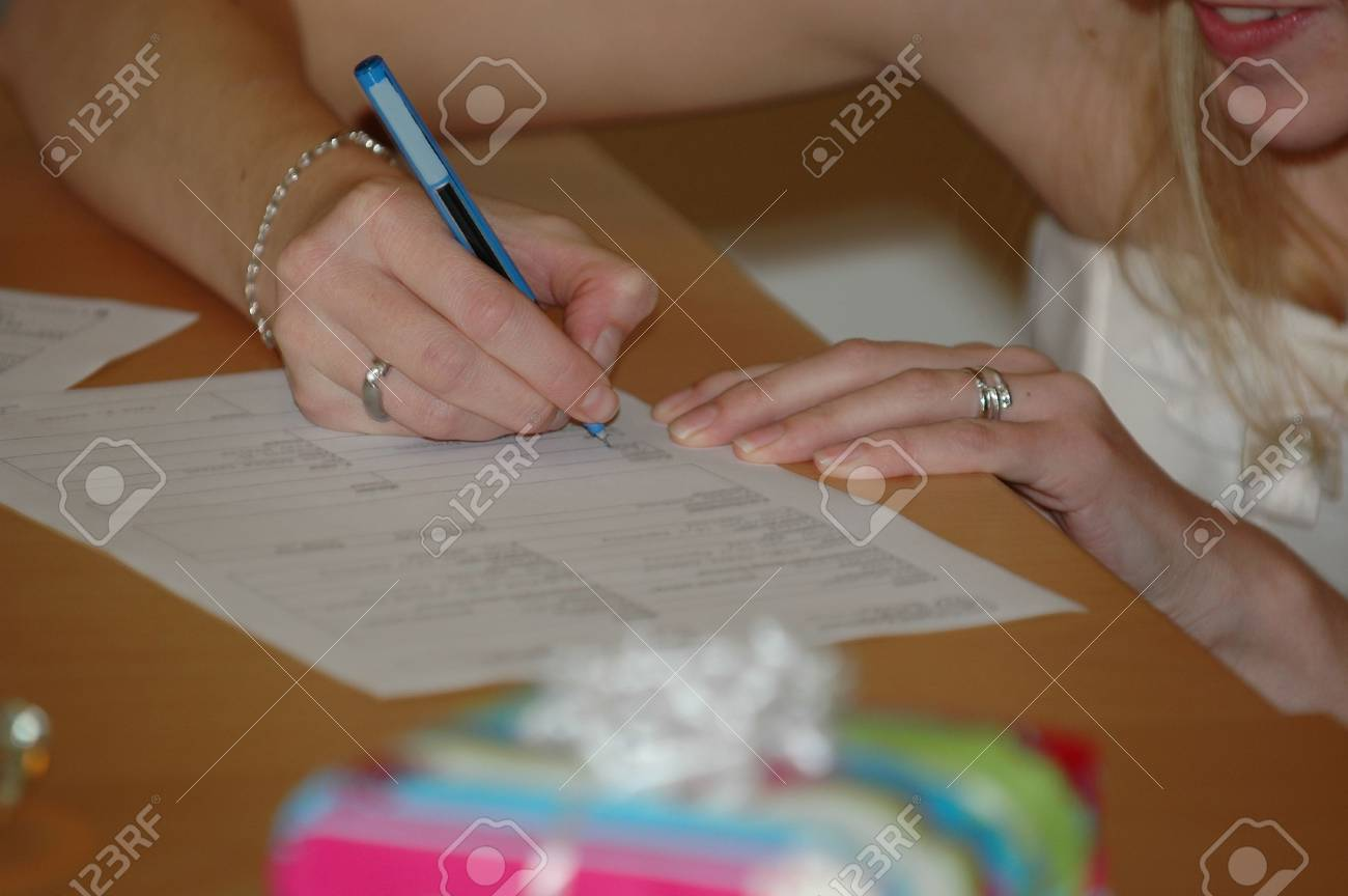 Bride signing the wedding contract. Note that all the tekst is in blur. Stock Photo - 706804