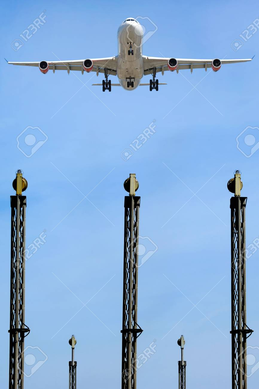 A plane is flying over the landing lights in an airport. Stock Photo - 2942043
