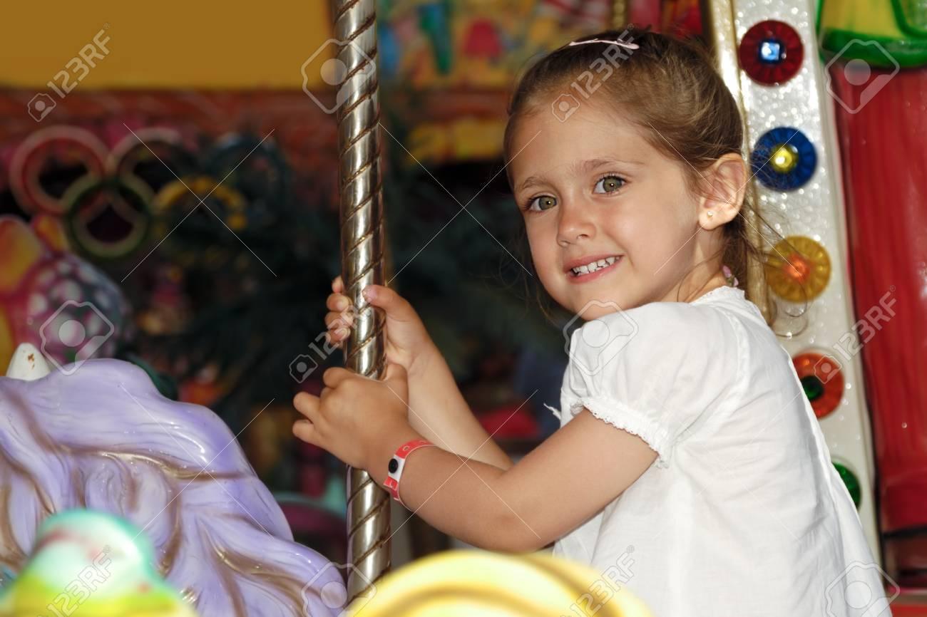 Un niño sonriente dulce está sentado sobre el caballo en el carrusel Foto de archivo - 8900141