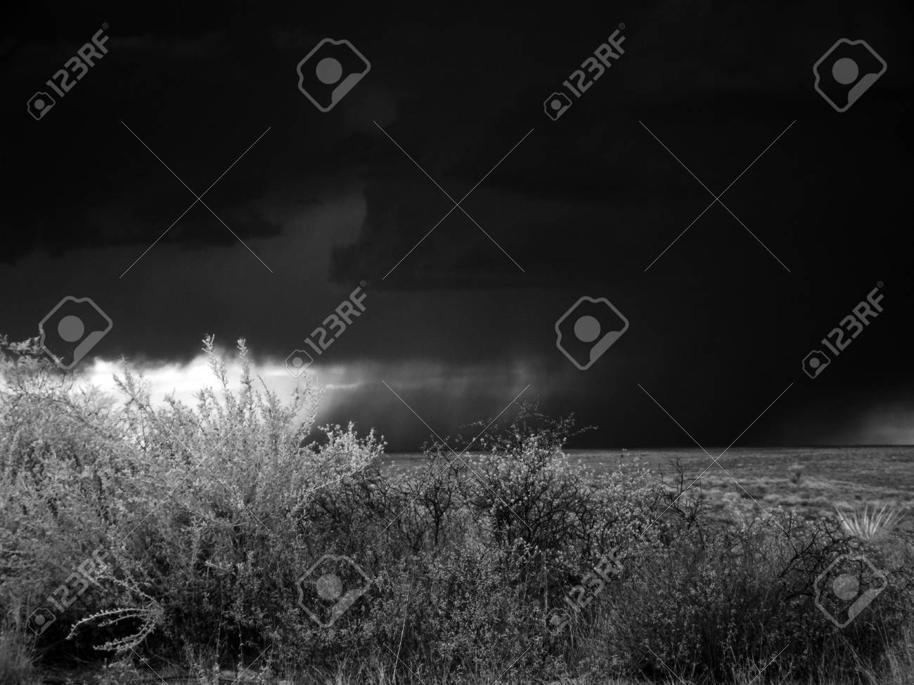 A black and white infrared photograph of a storm over the canyon