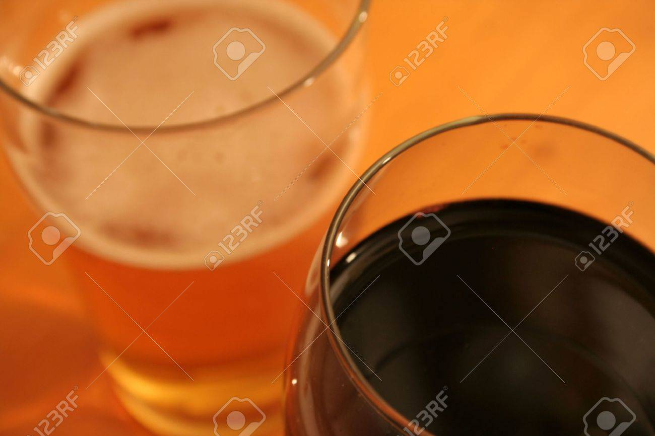 A pint of beer and a glass of red wine set against a wood grain table. Stock Photo - 312428