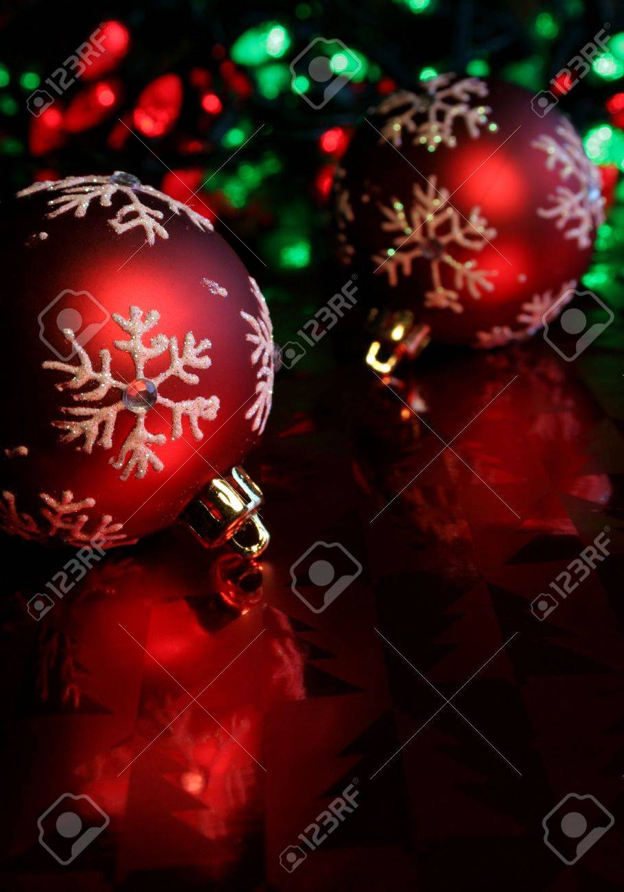 Two red christmas baubles illuminated on glossy red paper. Stock Photo - 631184