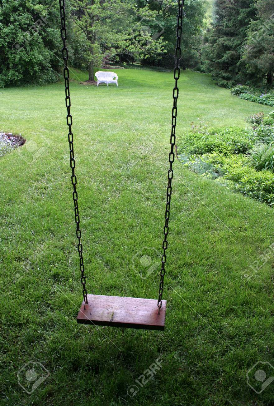 an old wooden swing sitting in a lush backyard stock photo