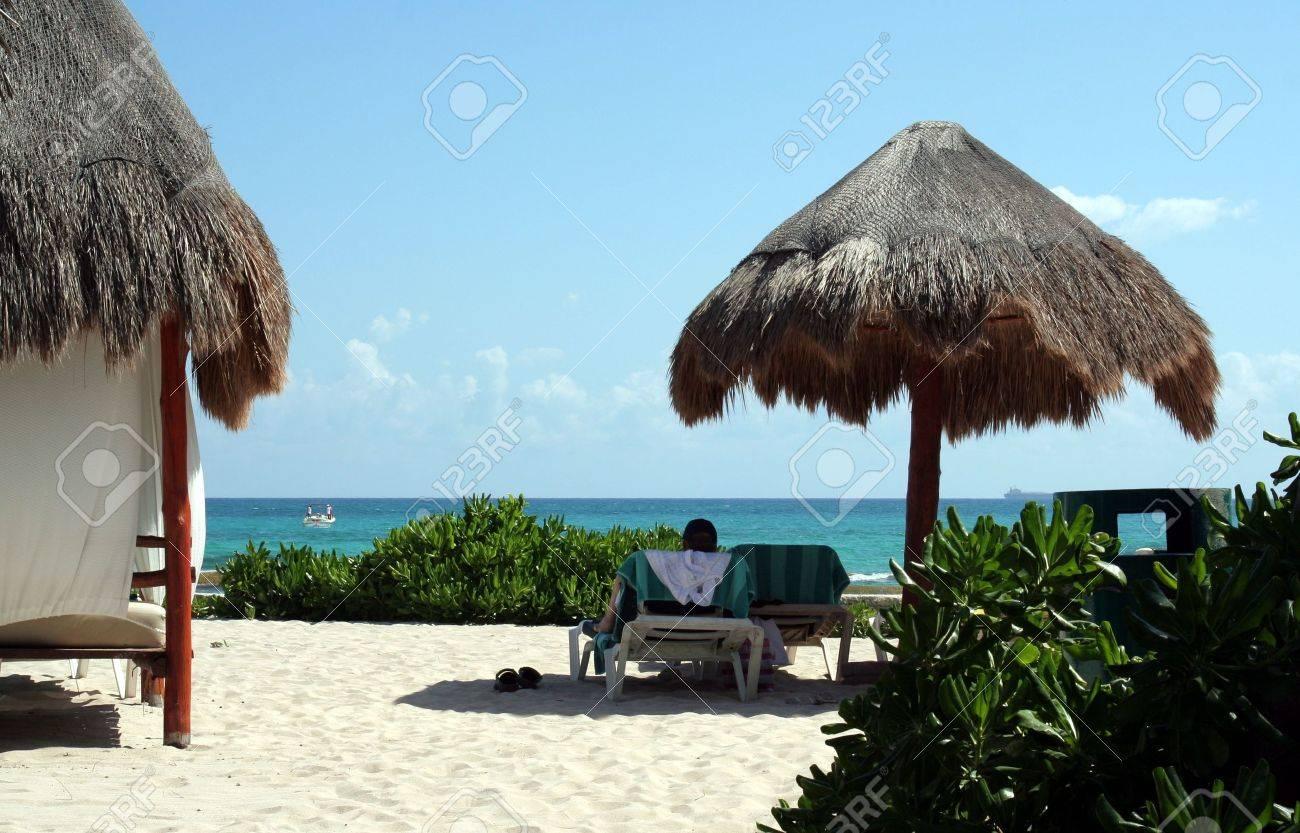 A man lying on a beach chair in the shade at a tropical beach. Stock Photo - 2731445