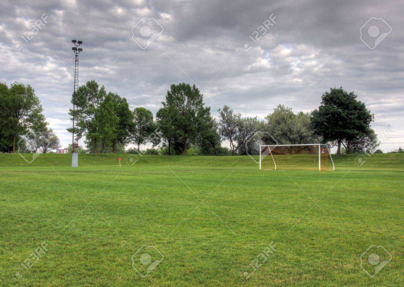 A cloudy unoccupied soccer field with trees in the background a cloudy unoccupied soccer field with trees in the background hdr photograph stock altavistaventures Gallery