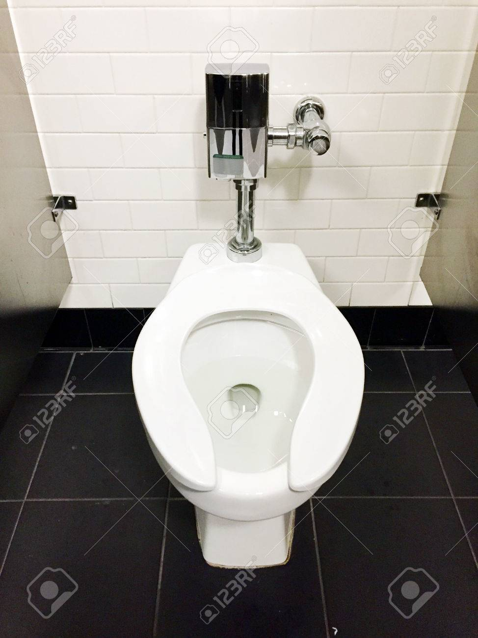 White Toilet In Metal Stall In Public Bathroom On Black Tile.. Stock ...