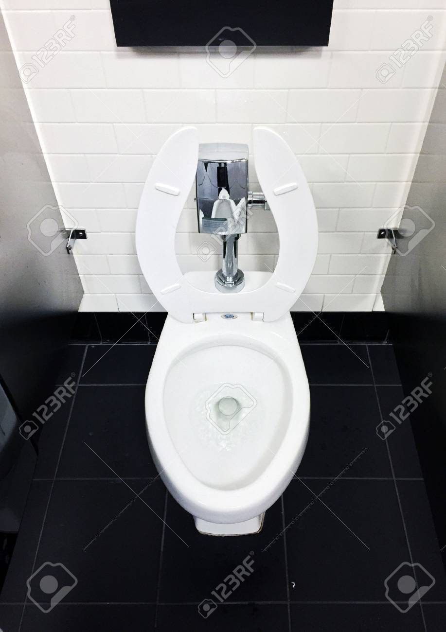 White Toilet In Workplace Office Bathroom On Black Tile Floor Stock