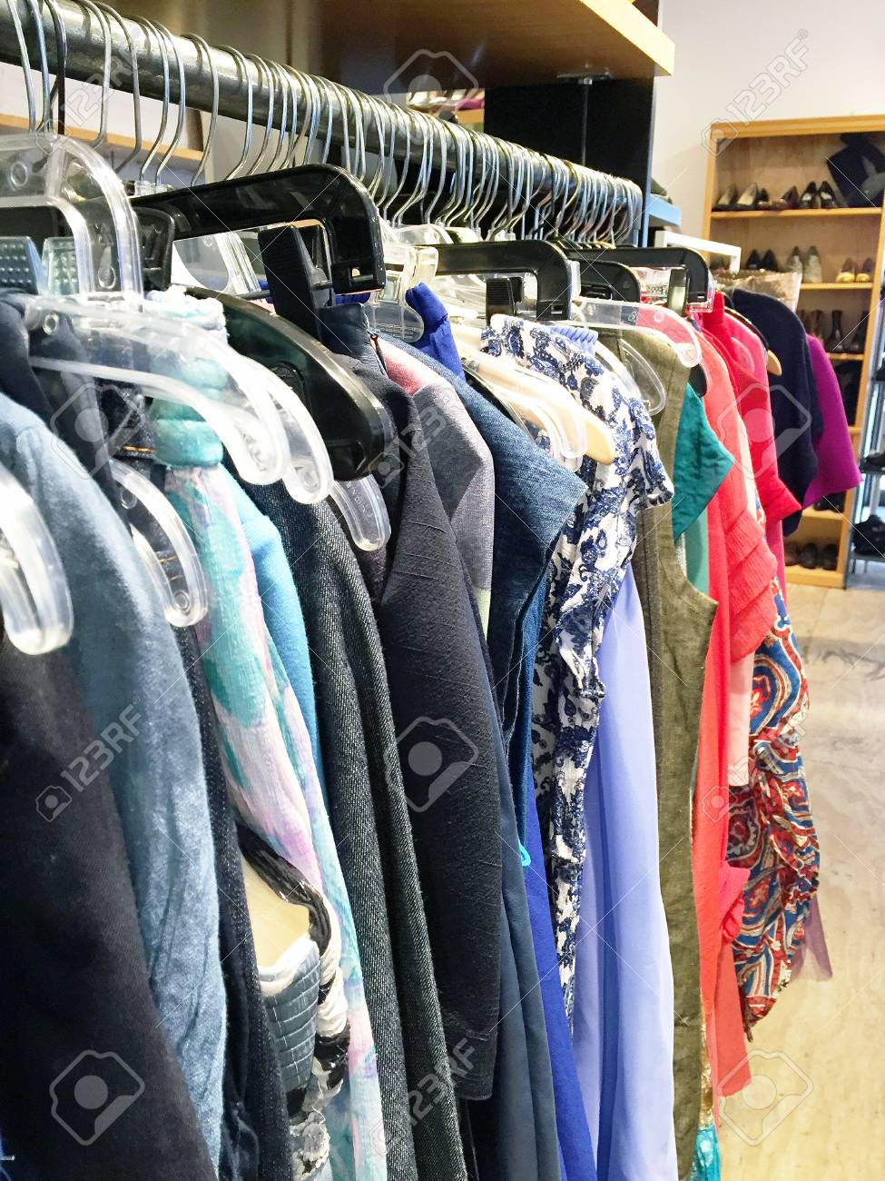 Women's clothing (pants, shirts, scarves) hanging on clothing..