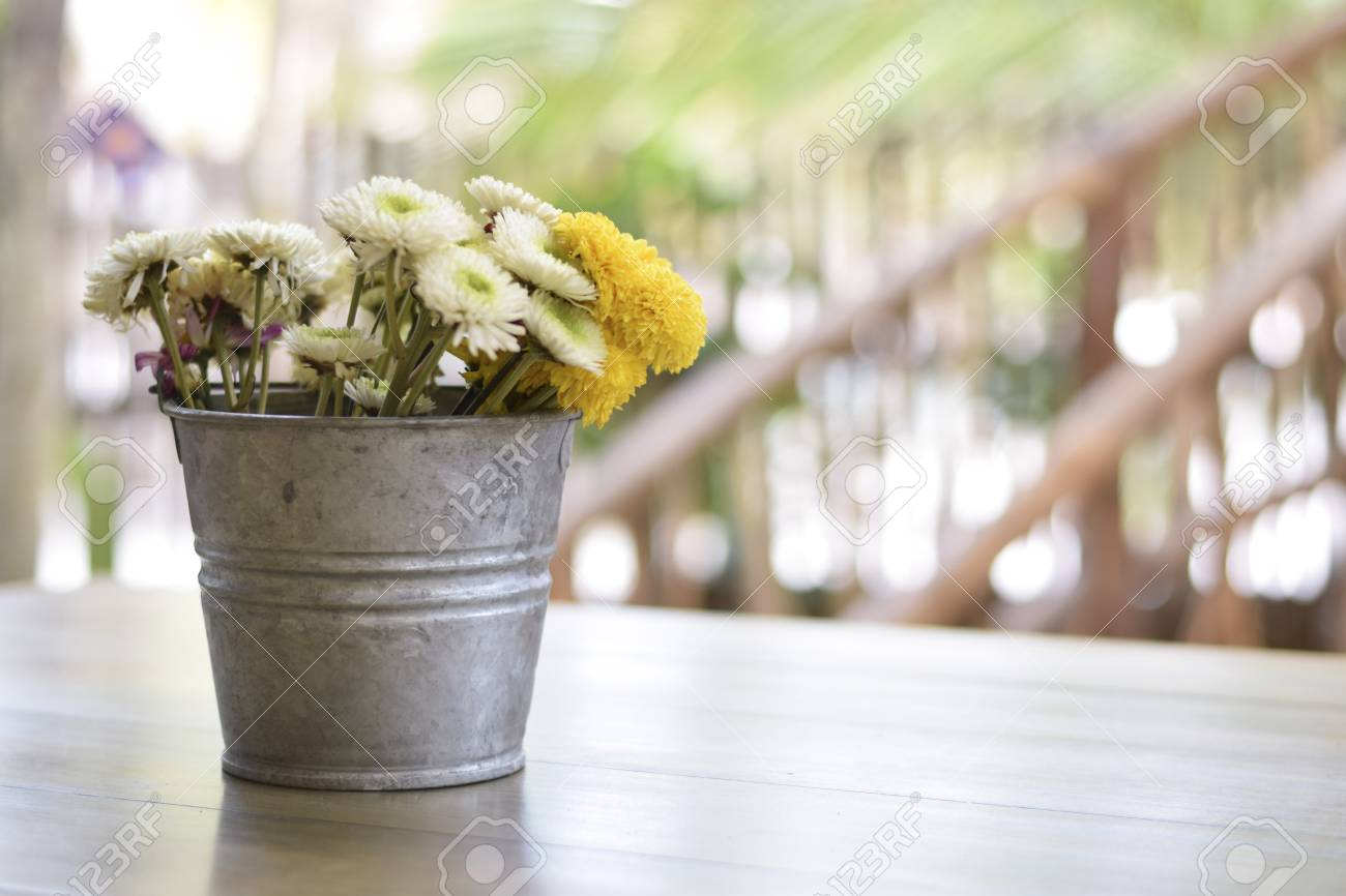 Rustic Vintage Metal Flower Pot On A Wooden Table With Daisies Stock ...