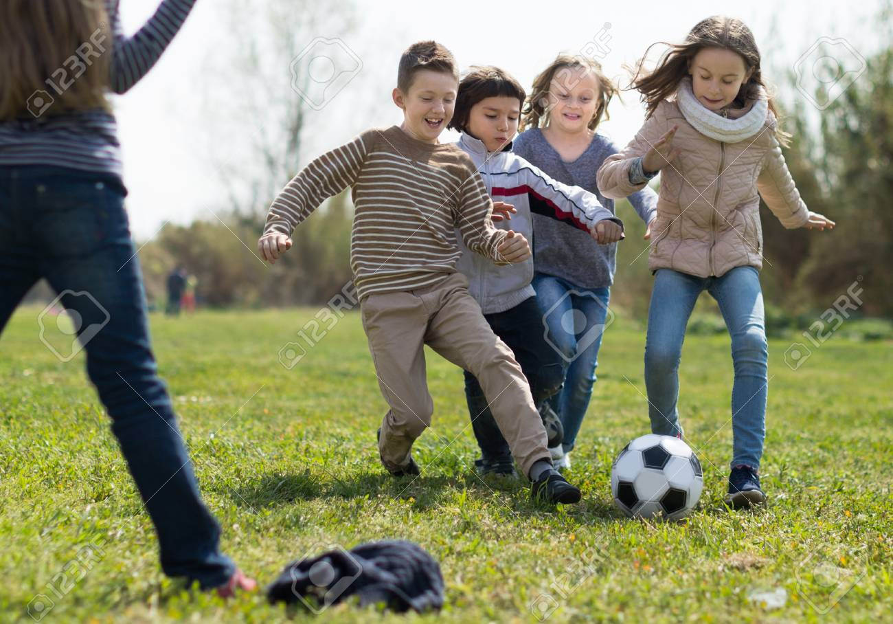 Chicas Activas Y Nino Jugando Futbol En El Parque En Otono Fotos