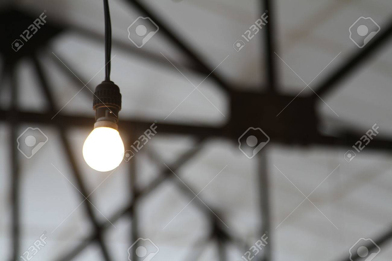 bare industrial light bulb with roofing girders low key stock photo
