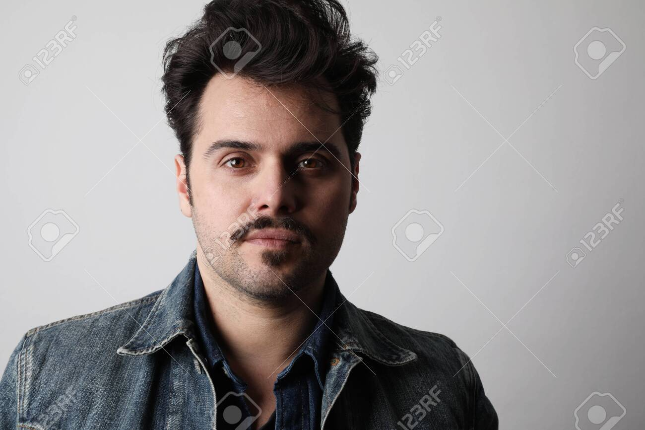 Headshot of serious stylish man looks straight with confident expression, wears denim jacket, isolated. - 144913986