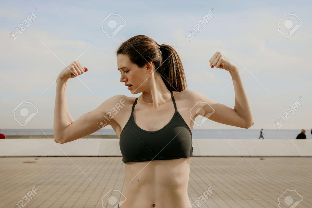 Portrait of young sporty woman showing biceps posing outdoor. - 159377821