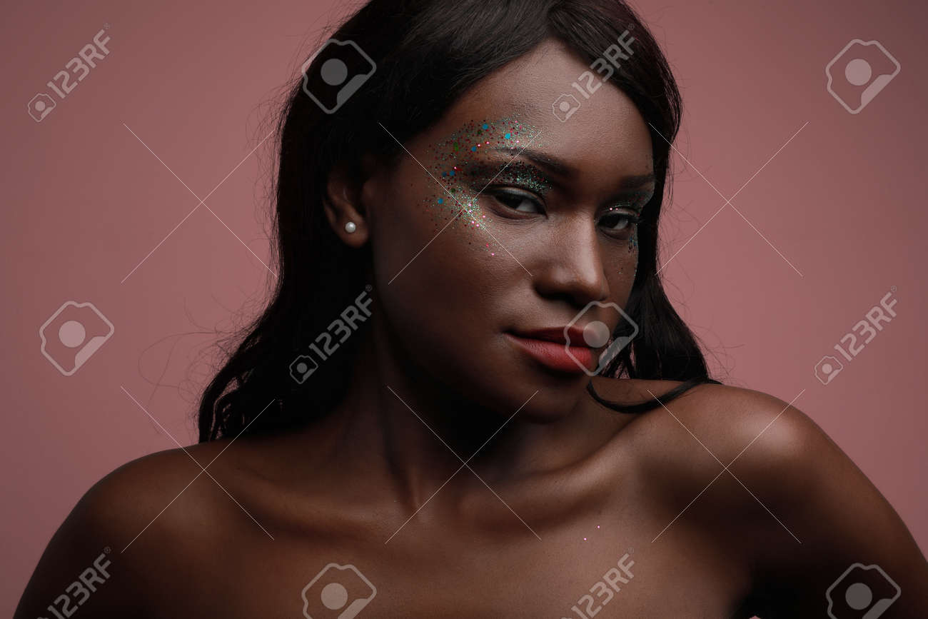Portrait of young black woman posing in the studio, with glittery make-up. - 169386496