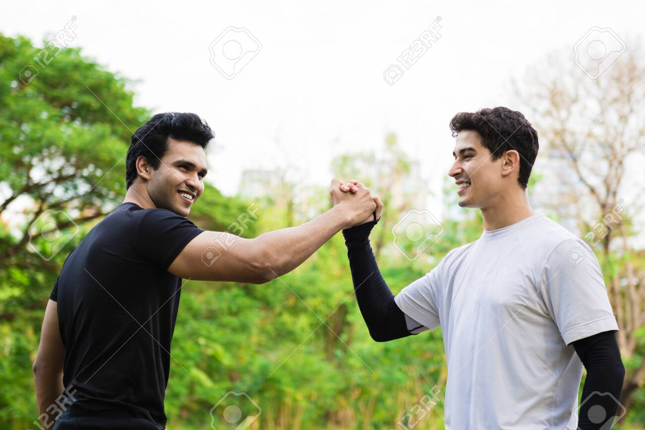 Happy friends giving high five outdoors in a park - 148628800