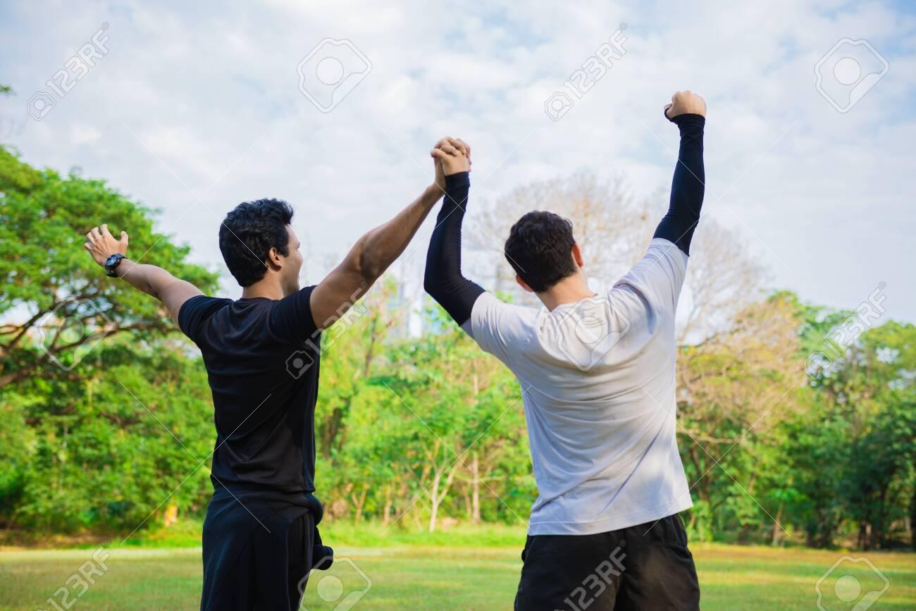Men feeling cheerful and hand up in the park - 148628802