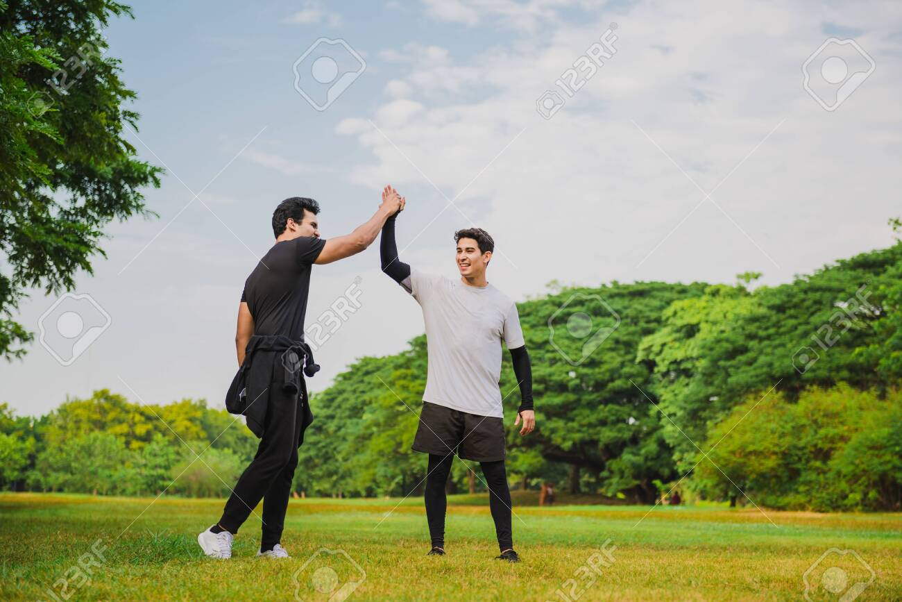 Two men giving high five in the park after breaking a new time record - 148628807