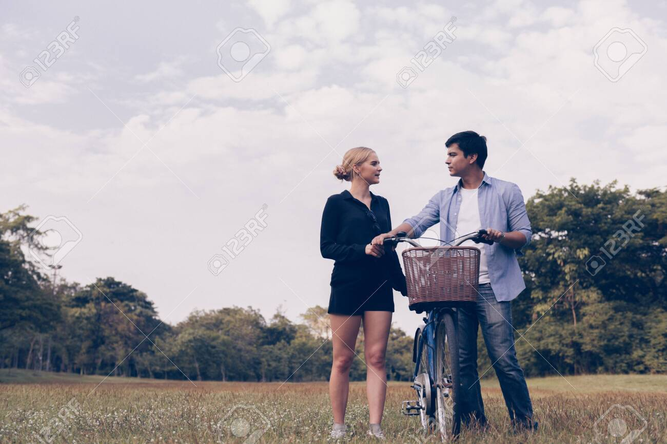 Happy young couple going for a bike ride on a sunny day in the park. - 148628568