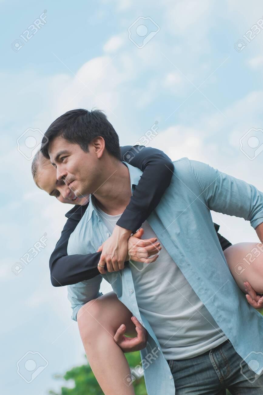 Boyfriend carrying his girlfriend on piggyback. - 148628570